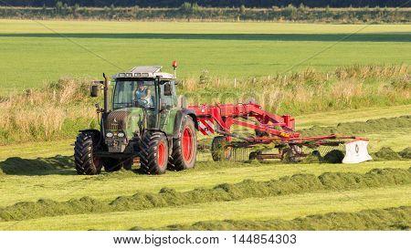 ACHTERHOEK NETHERLANDS - AUG 16 2016: Fendt tractor mowing grass farmland