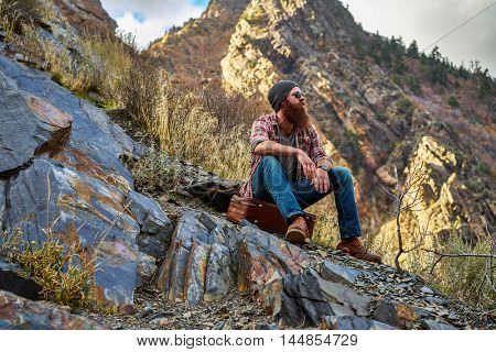 bearded hipster enjoying some chill time on mountain top