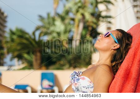 Side view of adult woman in bikini and sunglasses sunbathing on deckchair on resort