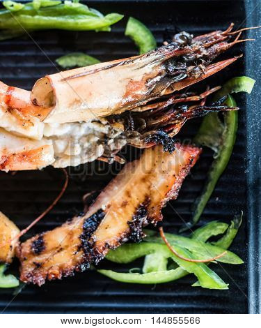 appetizing pieces of roasted seafood with sweet pepper on black plate closeup