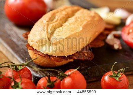 closeup of a Spanish bocadillo de chorizo, a sandwich made with sliced chorizo, a pork sausage typical of Spain, on a rustic wooden table with some tomatoes and garlic cloves
