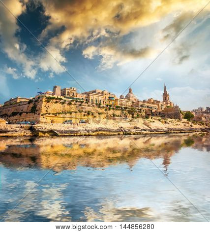 view on Valletta with its architecture from the sea at sunset with reflection