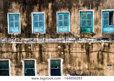 dirty neglected house with row of colorful windows in poor african region