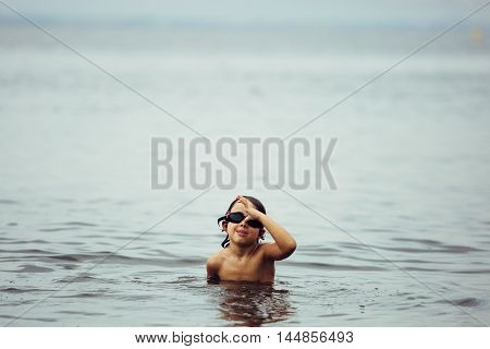 Portrait of funny boy making faces at camera while swimming in sea wearing goggles.Copy space