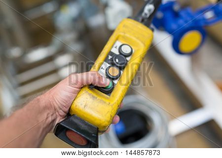 Industrial worker pushing on button of machinery control panel in manufactury.