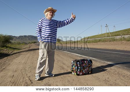 Hitchhiking travel elderly man at the route