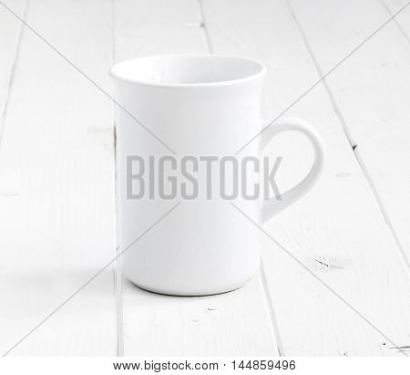 white empty cup on planked wooden surface