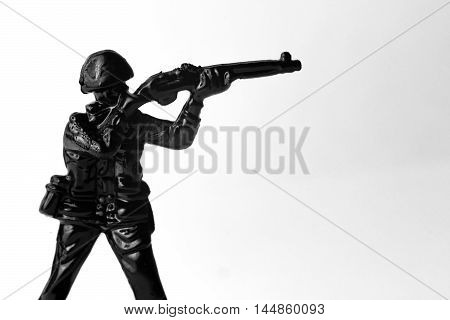 Dramatic toy army soldier aiming rifle in black and white image
