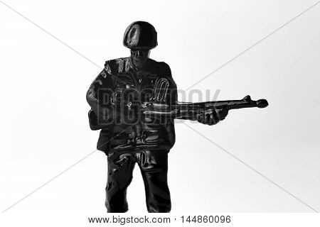 Dramatic toy army soldier marching to battle black and white image