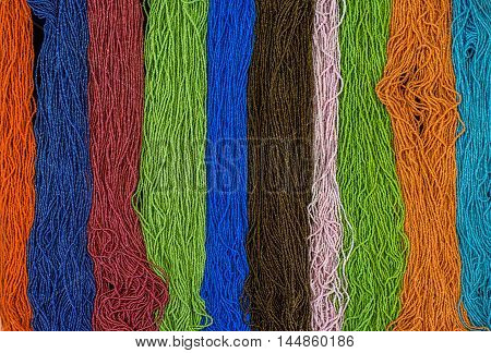 Background rainbow of colorful beaded necklaces and bracelets
