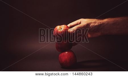 Conceptual composition of a healthy food three apples and a man's hand.