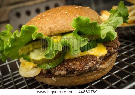 Cheeseburger on a whole wheat bun with skins on fries and jalapeno