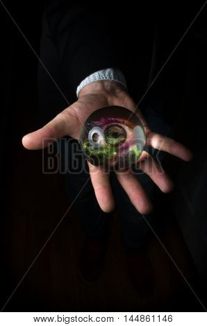 Holding third eye in fortune teller magic crystal ball