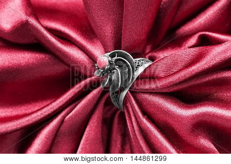 Vintage silver ring on draped red satin as a background