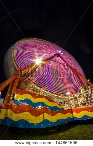 Summer carnival ferris wheel at night with light blur time lapse