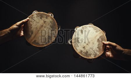 Just a two interesting wooden tambourines in front of black background.