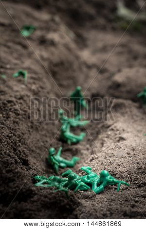 Green toy soldiers in the dirt defending the trenches