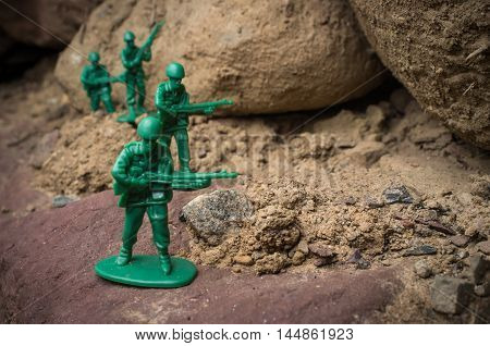 Toy soldiers march along rocky cliffs in natural environment