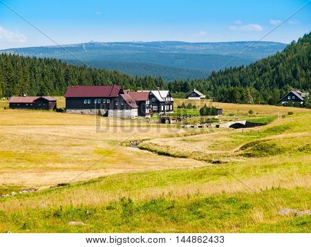 Large green meadows and rural mountain houses of Jizerka Village with Giant Mountains, or Krkonose, on the background, Jizera Mountains, Czech Republic.