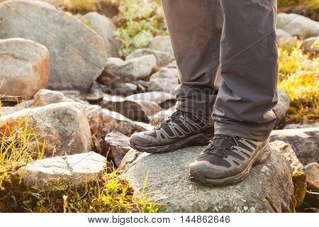 hiker standing on rock, legs in boots