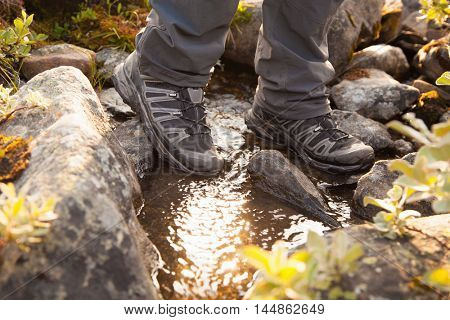 hiker crossing a river. legs in boots