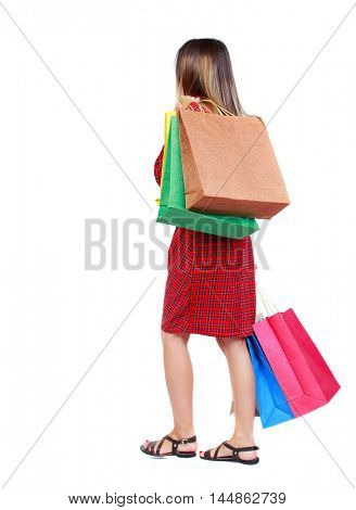 back view of going woman with shopping bags . girl in red plaid dress is thrown away in the back with shopping bags.
