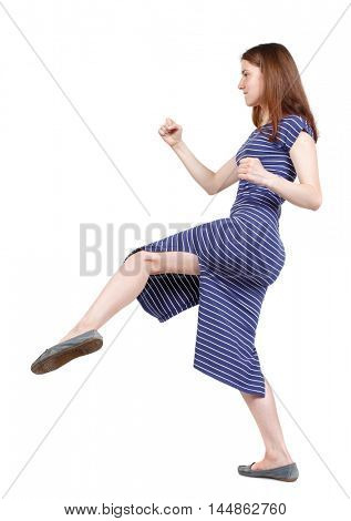 skinny woman funny fights waving his arms and legs. brunette in a blue striped dress in a fighting stance.