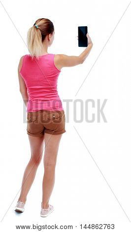 back view of standing young beautiful woman using a mobile phone. Isolated over white background. Sport blond in brown shorts looks at the plate.
