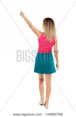Back view of pointing woman. beautiful girl. Rear view people collection. Isolated over white background. Blonde in a red sweater and green skirt went off pointing to the sky.