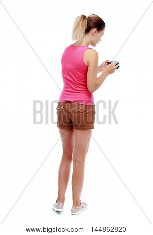 back view of standing young beautiful woman and using a mobile phone. Isolated over white background. Sport blond in brown shorts photographed nothing on earth.
