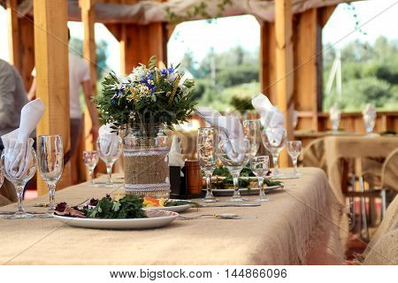 beautifully decorated wedding table with plates and napkins in nature.