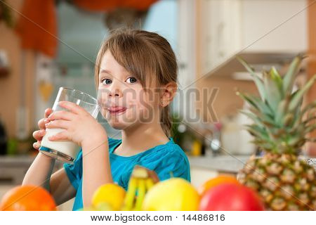 Healthy eating - Child drinking milk, lots of fresh fruit on the table in front