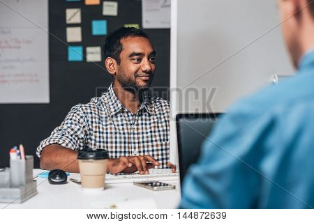Smiling designer sitting at his desk working on a computer while sitting in front of a colleague in an office