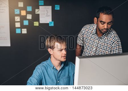Two designers collaborating on a project together in front of a computer while working in an office