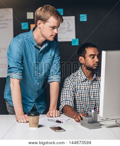 Two focused designers collaborating on a project together in front of a computer while working in an office