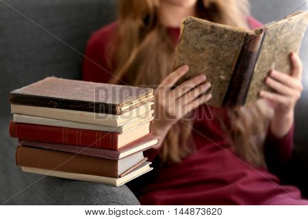 Stack of books and reading woman in armchair