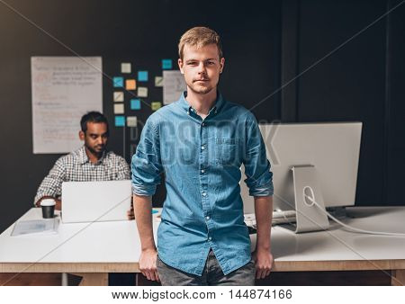 Portrait of a designer standing in an office with a colleague working on a laptop computer at a desk in the background