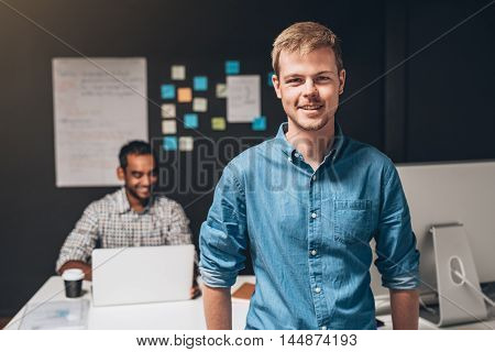 Portrait of a smiling designer standing in an office with a colleague working on a laptop computer at a desk in the background