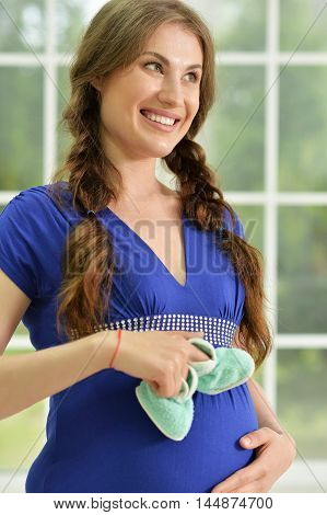 portrait of happy  Pregnant woman at home with small shoes for the unborn baby