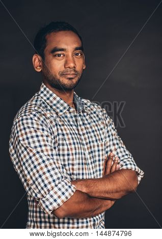 Studio portrait of a confident young entrepreneur standing with his arms crossed in front of a dark background