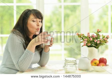 Senior woman with fruits and tea at home