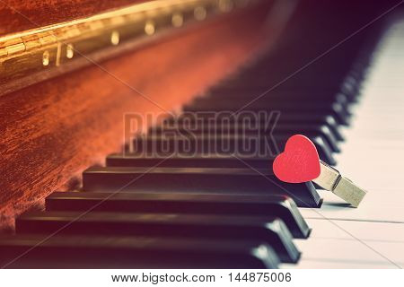 Piano keys with wooden red heart clip vintage retro color style selective focus on the red heart clip