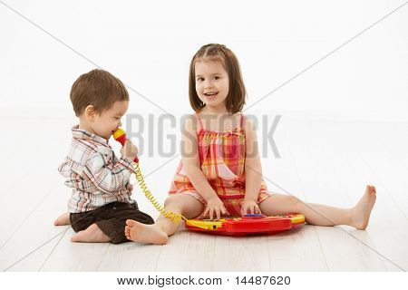 Happy kids playing on toy music instrument, little boy singing to microphone over white background.?