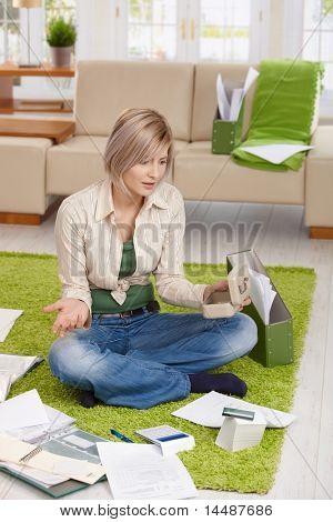 Frau, die Überprüfung von Dokumenten und Kreditkarten-Abrechnung, schockiert über Finanzlage, sitzt zu Hause auf