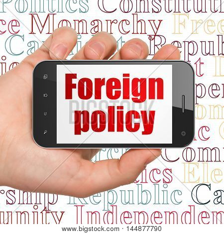 Political concept: Hand Holding Smartphone with  red text Foreign Policy on display,  Tag Cloud background, 3D rendering