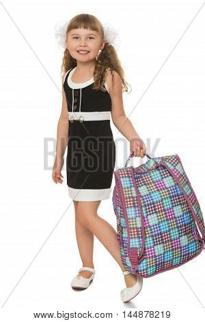 Laughing girl in the black school dress . The girl carries a satchel- Isolated on white background