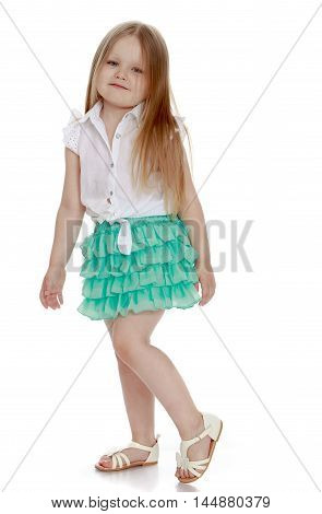 Little girl with long blond hair below the shoulders , in a short green skirt . Girl turned sideways to the camera .  - Isolated on white background