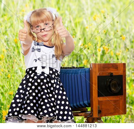 Adorable little blond girl wearing glasses and fancy dress polka dot advertises the old wooden camera.On the background of green grass and yellow wild flowers, blurring the background.
