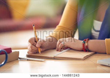 Hands of woman writing in her textbook