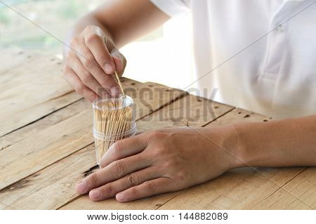 woman pick wooden toothpick from plastic box on wood table for cleaning teeth